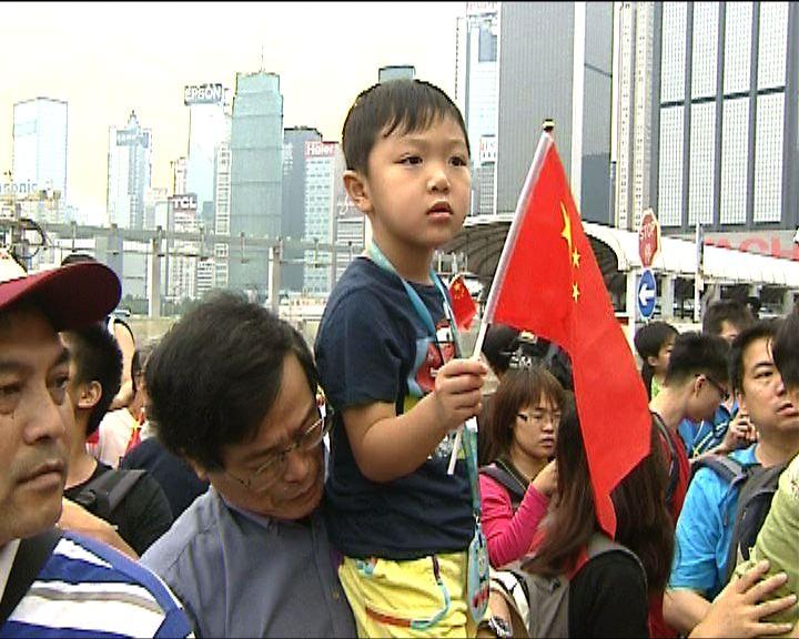 有家長帶子女觀看國慶升旗儀式