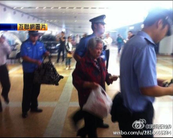 一名老婦於北京首都機場放炮仗