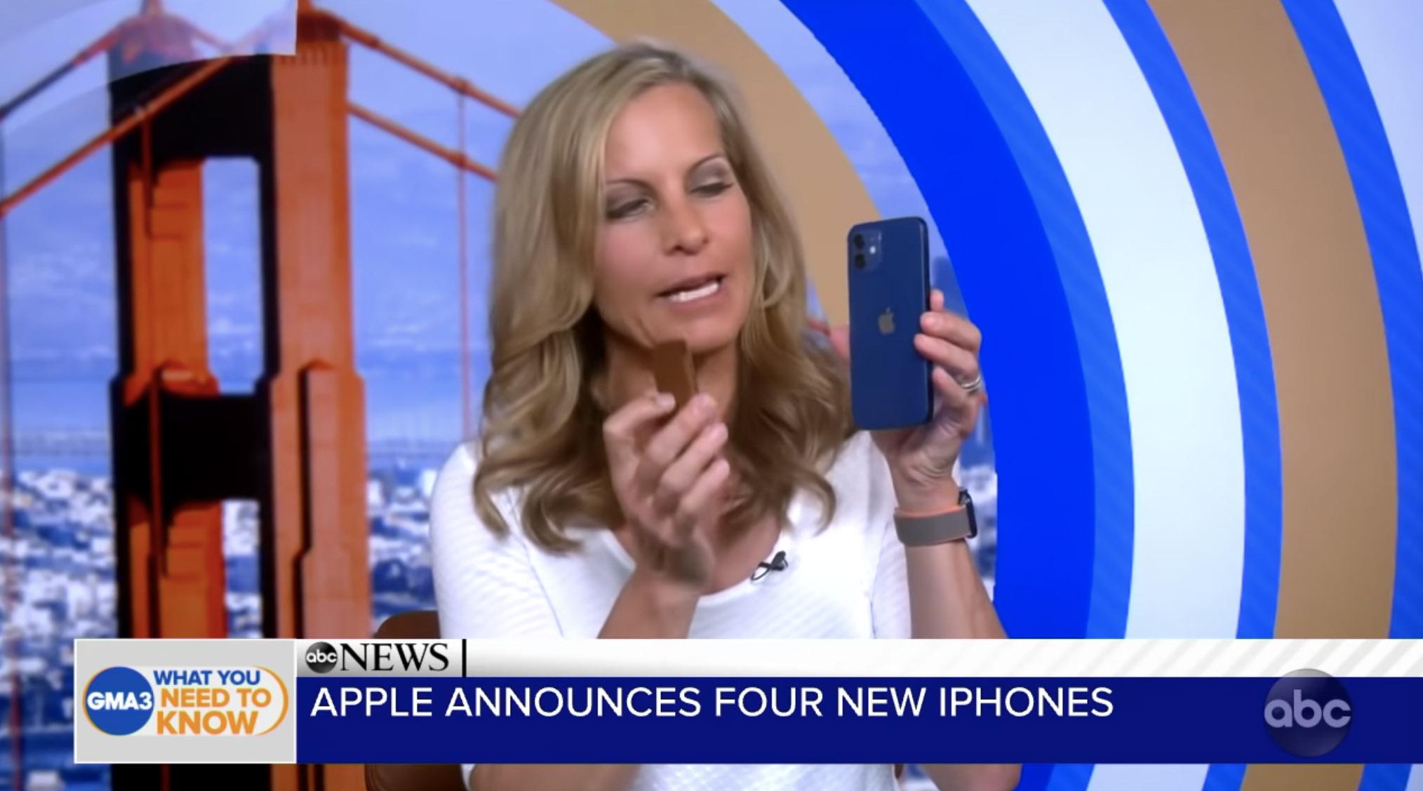 記者手上拿著 iPhone 12 藍色