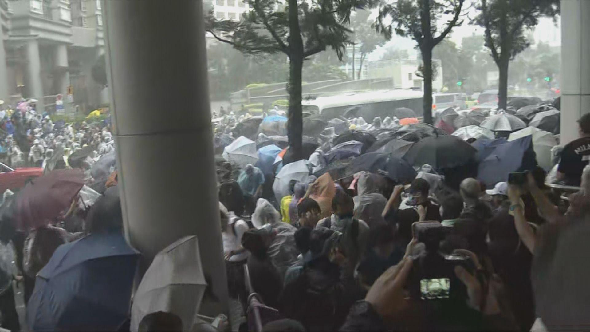 警車駛經法院大樓被示威者包圍破壞