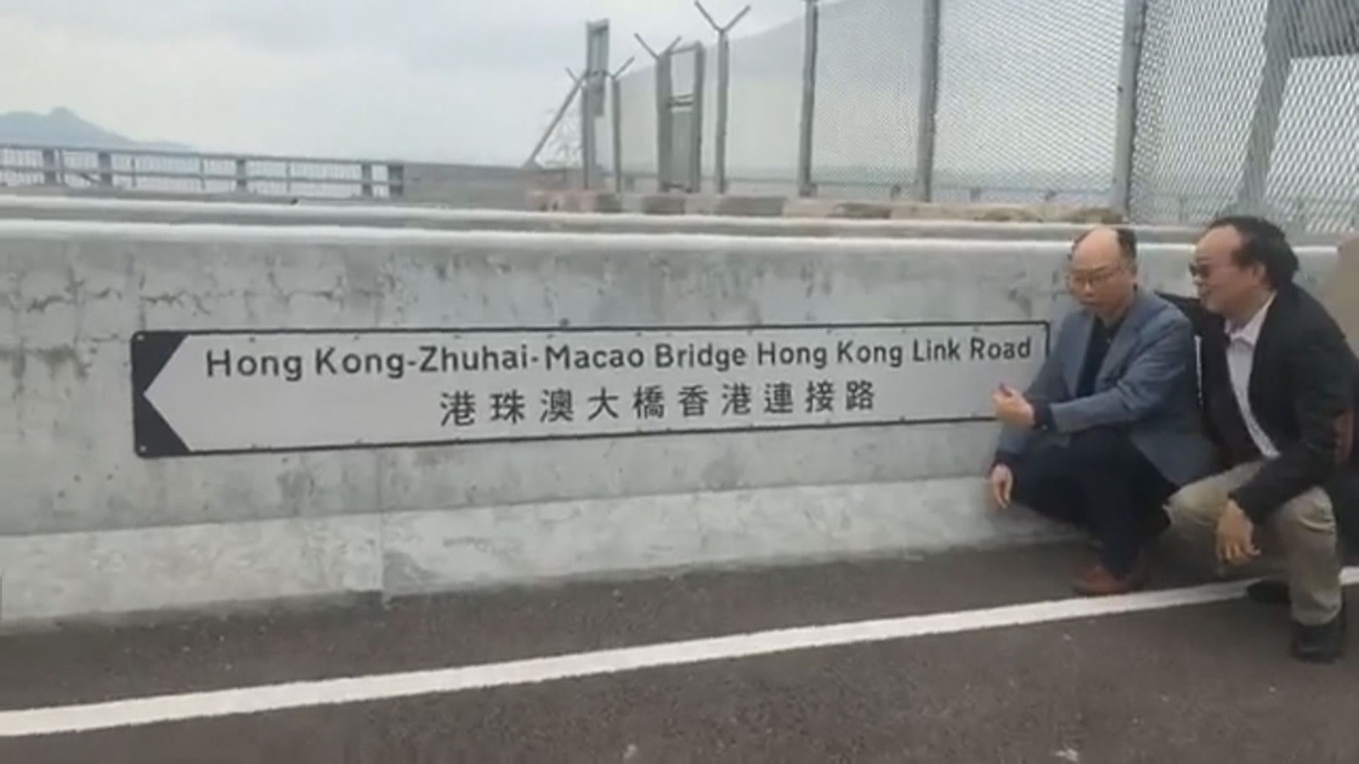 陳帆跟議員在大橋粵港分界線前的路牌合照