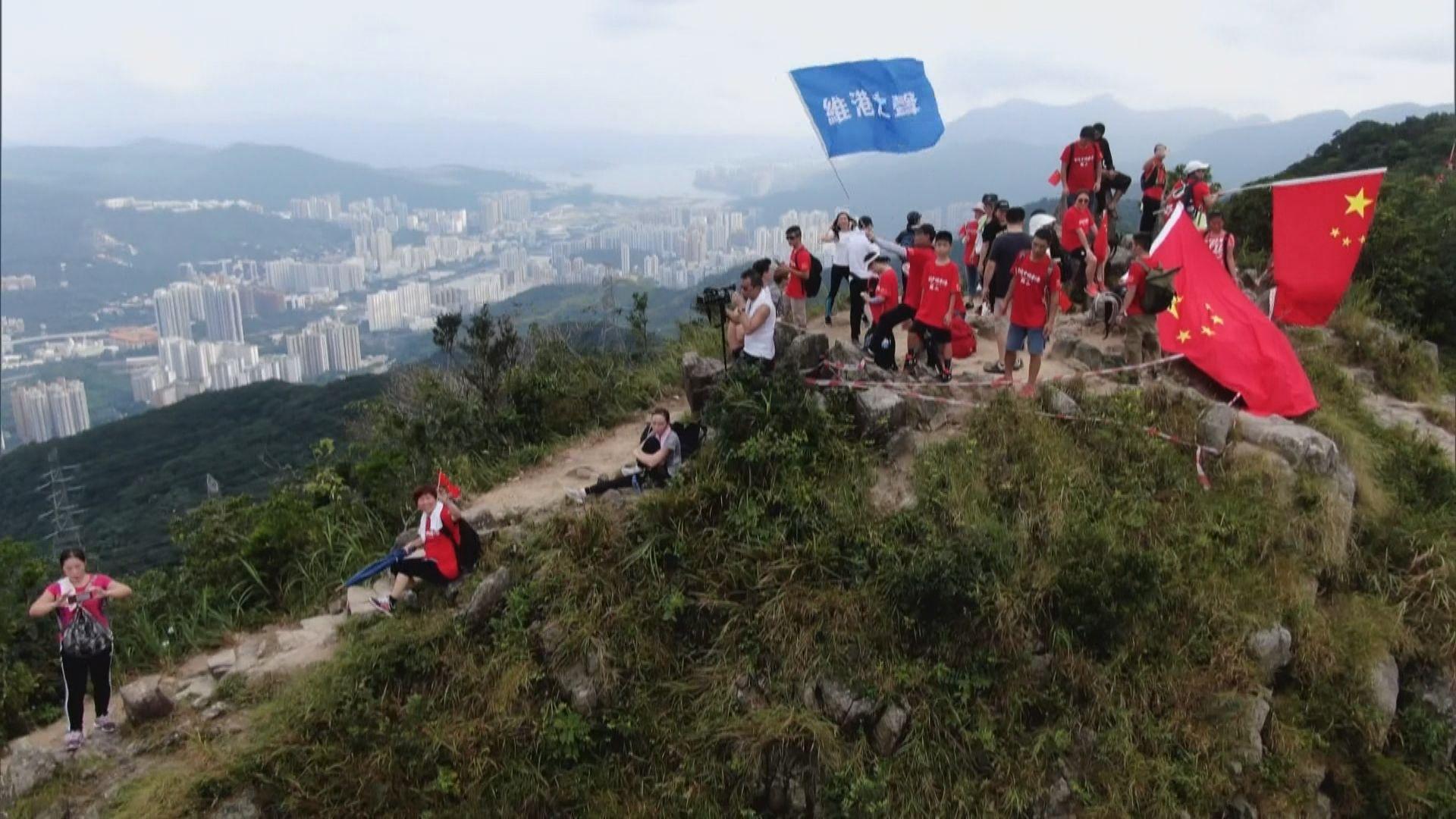 十多名市民登上獅子山山頂揮舞國旗