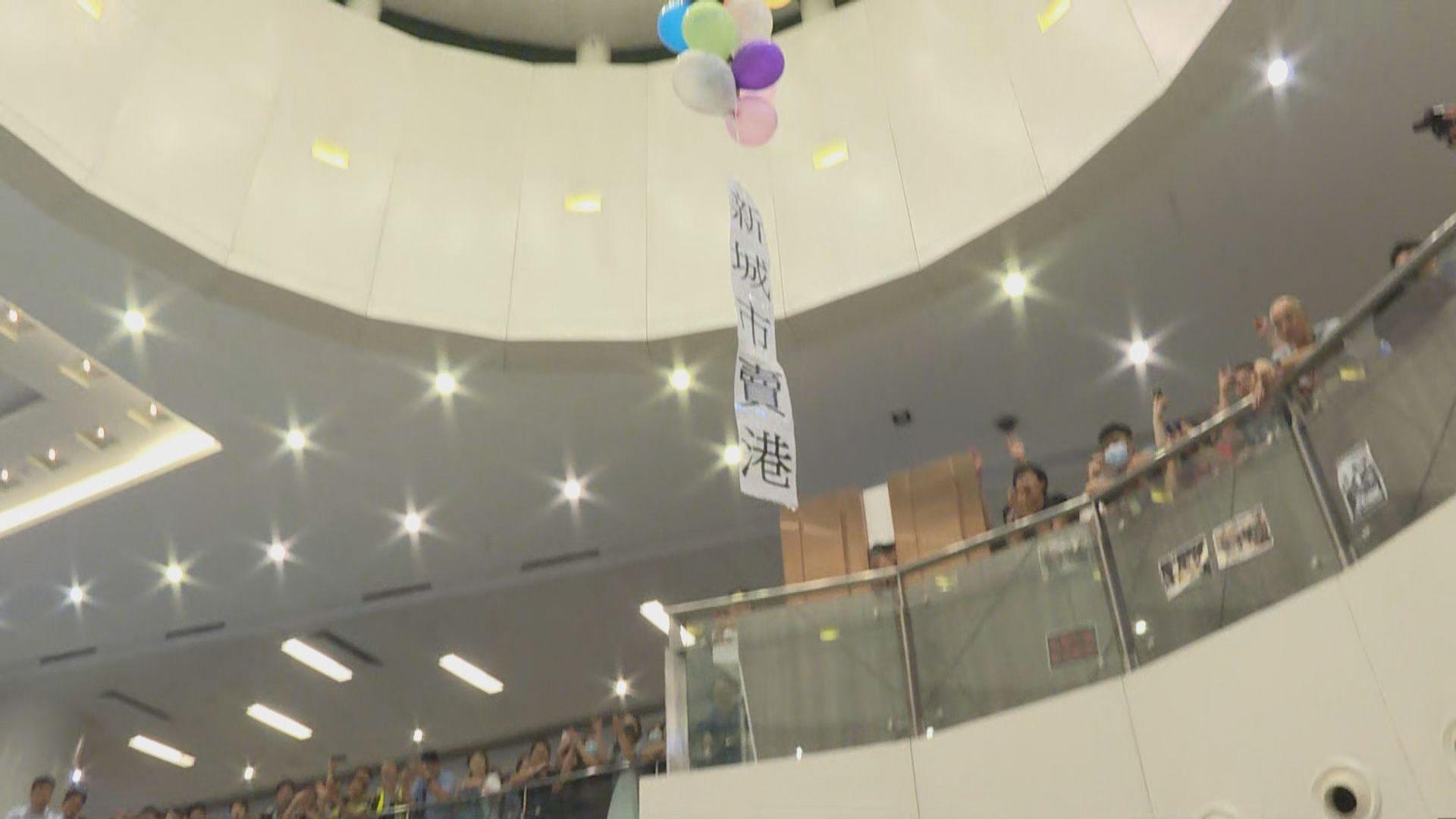 新城市廣場內有人將示威標語汽球放上半空