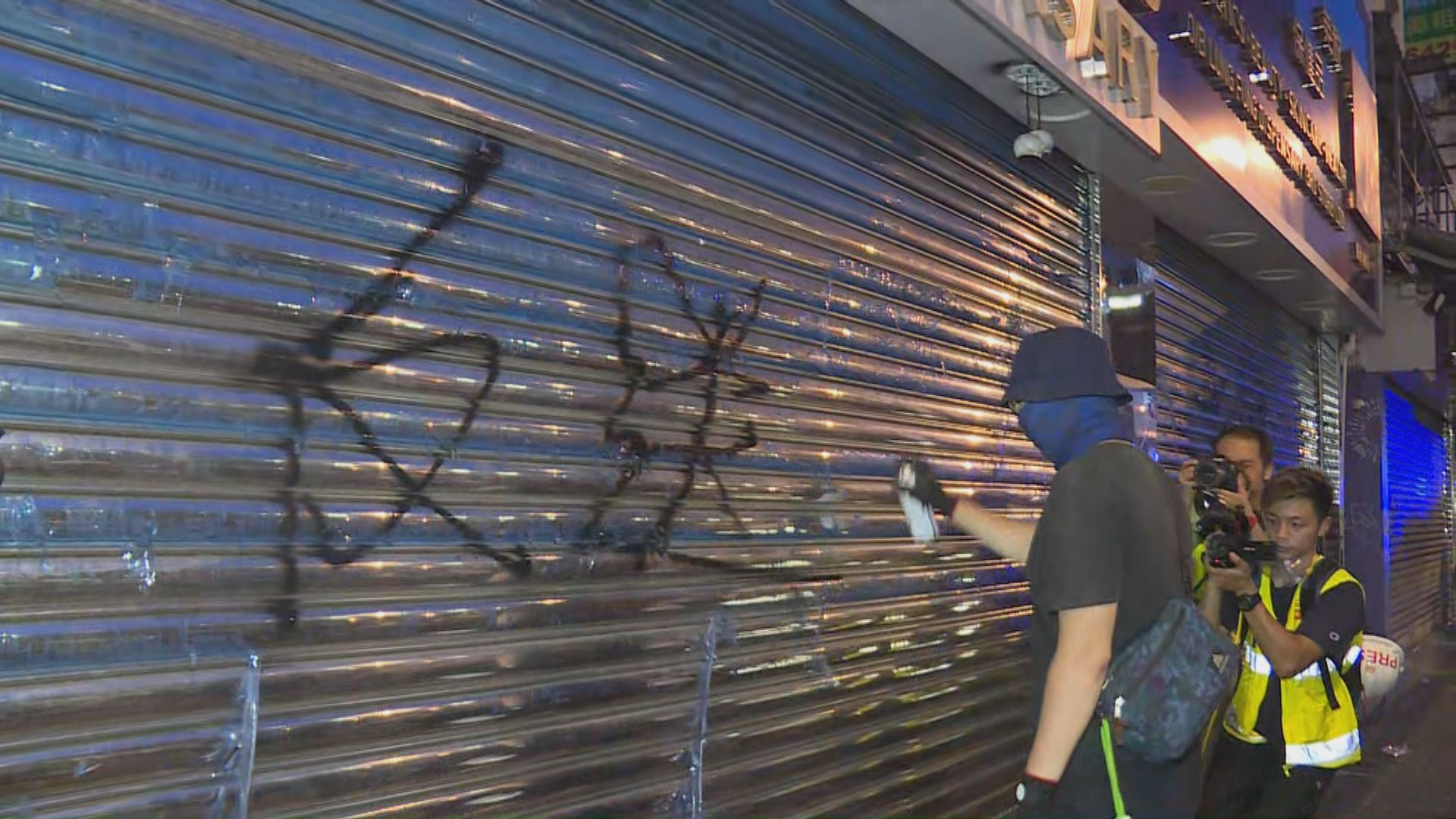 有示威者拆毀藥房招牌及在鐵閘噴大字