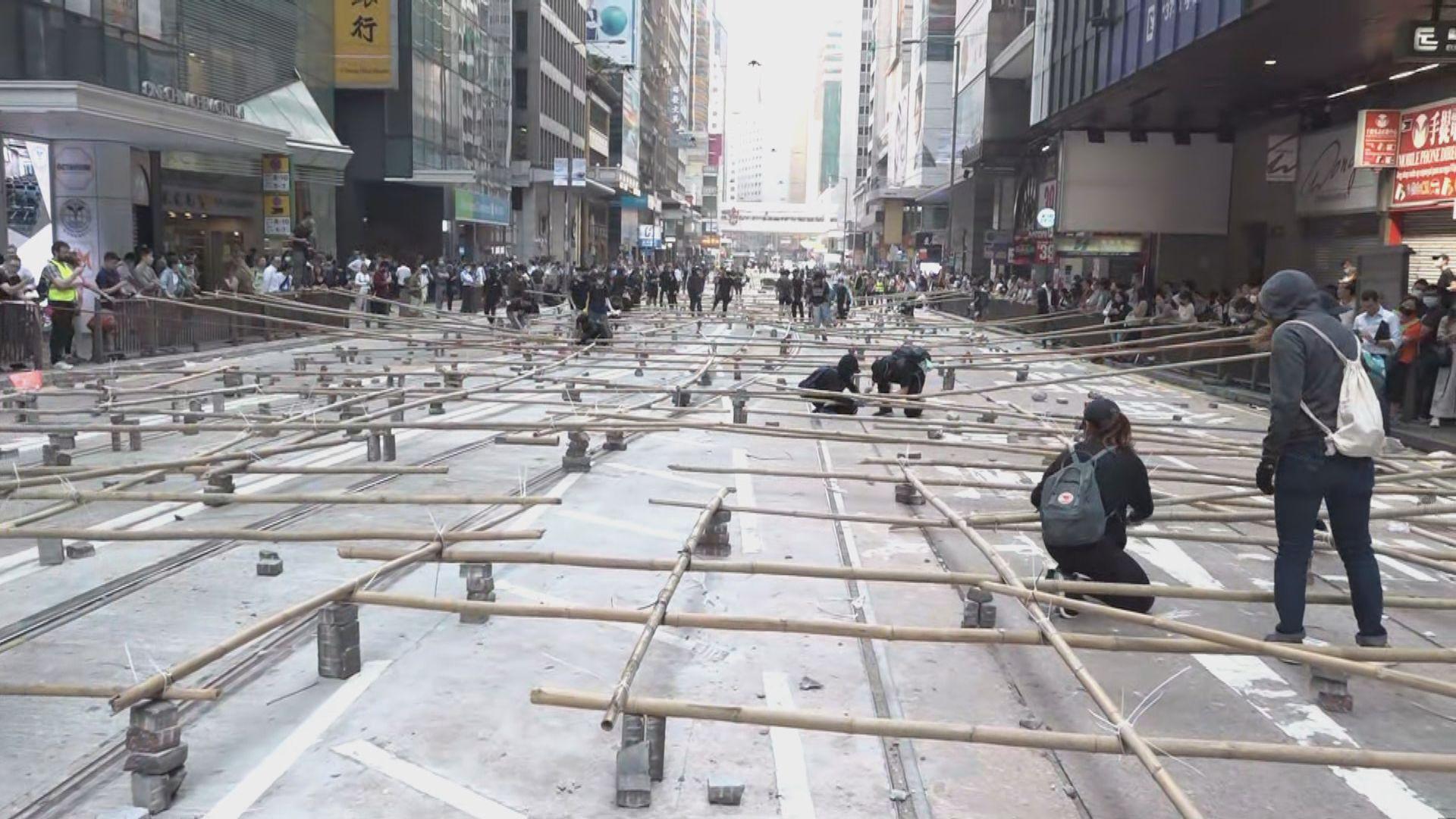 中環示威者以長竹和磚頭在電車路設路障